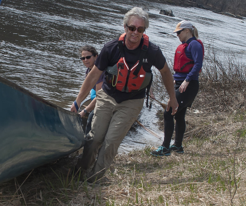 """Bill Kelley helps to pull the Kenduskeag Screamah out of the water at the """"Shopping Cart"""" portage on Kenduskeag Stream."""