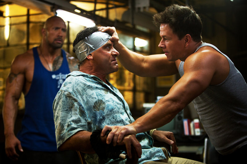 "Dwayne Johnson, left, Tony Shalhoub and Mark Wahlberg star in ""Pain & Gain,"" based on a true story about friends who kidnapped a rich gym client to try to make him sign over his assets to them."