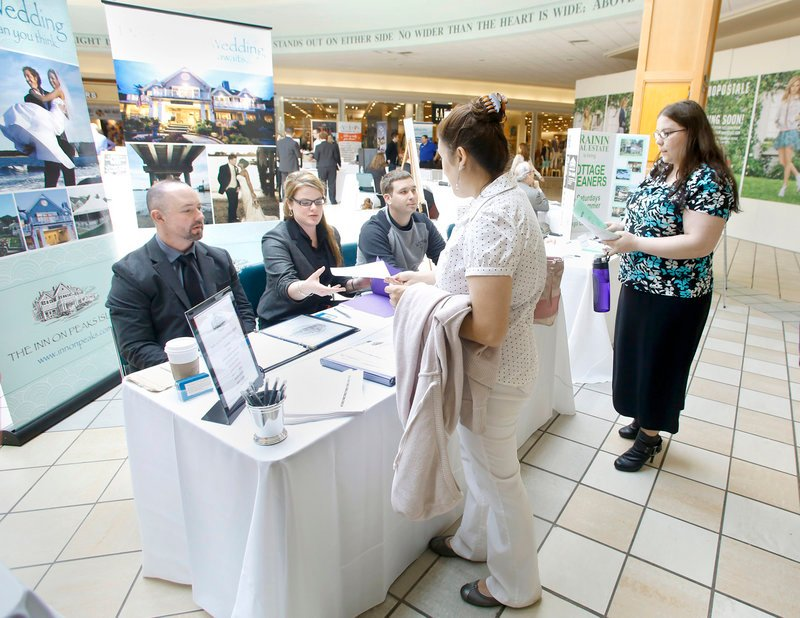 Ashley Dombrowik of Saco gives her application to Amanda Conley of The Inn on Peaks Island, as another applicant waits, at the job fair at the Maine Mall Wednesday. With Conley from the inn are Jayson Mathieu, left, and Andrew Hobin.