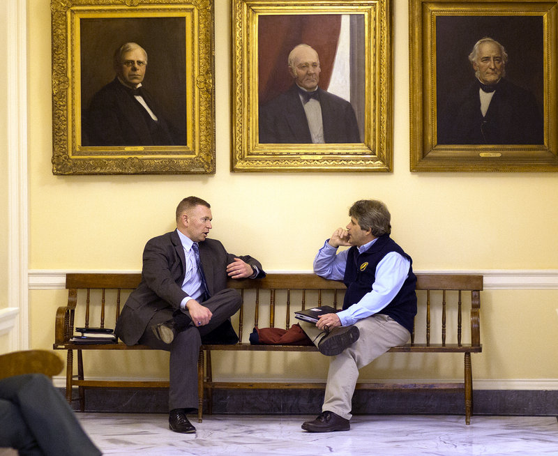 Maj. Christopher Grotton of the Maine State Police, left, speaks with David Trahan, executive director of the Sportsman's Alliance of Maine, about gun issues in a hallway at the State House in Augusta last Wednesday.