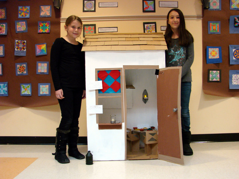 """Wells Elementary School students Amanda Ring and Isabella DeAngelis stand by a miniature cardboard replica of a safe house they created as part of a display for a class study on the """"Underground Railroad"""" recently."""