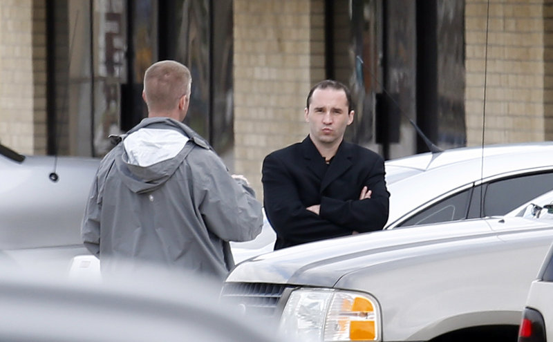 Everett Dutschke, right, confers with a federal agent Wednesday near the site of a martial arts studio he once operated in Tupelo, Miss. Dutschke was arrested Saturday.