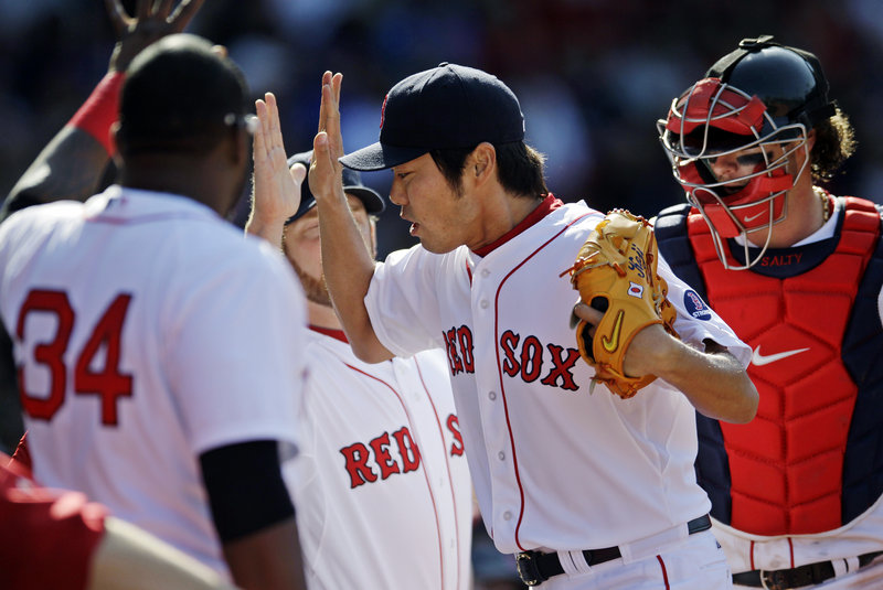 Relief pitcher Koji Uehara is congratulated by David Ortiz (34) and other teammates after working the eighth inning during Sunday's victory over Houston at Fenway Park.