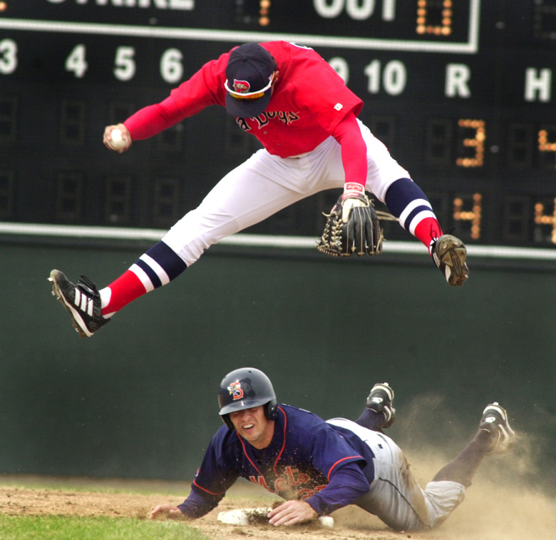 Staff Photo by Jill Brady, Sunday, April 18, 2004: Sea Dogs short stop #14, Kenny Perez, jumps over Mets #23, Chris Basak, after making the first out of the second inning during Sunday's game at Hadlock Field in Portland. Jill Brady Baseball
