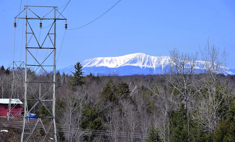 In this April 2011 file photo, Mt. Katahdin looms over electrical transmission lines that lead to the closed Katahdin Paper Mill and other hydroelectric dams along the Penobscot River. A legislative committee is expected to vote Friday, May 23, 2013 on an ambitious proposal aimed at lowering Maine's high electricity and heating costs.