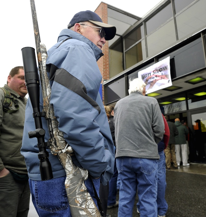 In this January 19, 2013 file photo, Sid Strom from Norway, ME waits for the opening for the Augusta Gun Show at the Augusta Civic Center. A Maine legislative committee supported expanding mandatory background checks on gun-show purchases.