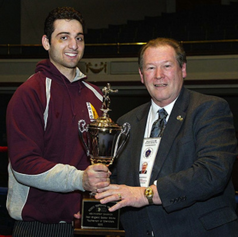 Tamerlan Tsarnaev, left, is shown accepting the trophy for winning the 2010 New England Golden Gloves Championship from Dr. Joseph Downes in Lowell, Mass., on Feb. 17, 2010. Authorities are trying to determine whether the now-dead Boston bombing suspect had a hand in the unsolved triple slaying of Tsarnaev's boxing partner.