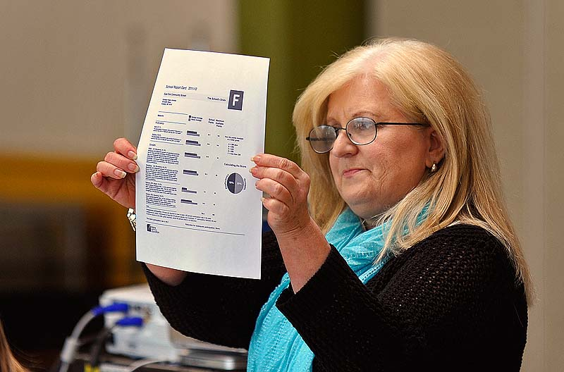 During a meeting with staff, East End Community School Principal Marcia Gendron holds up the report card indicating a letter grade of F that the school received Wednesday after the LePage administration released its new education grading system.