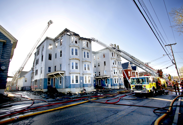 Firefighters battle a fire that destroyed multiple vacant apartment buildings on Bartlett Street in Lewiston on May 6, 2013.