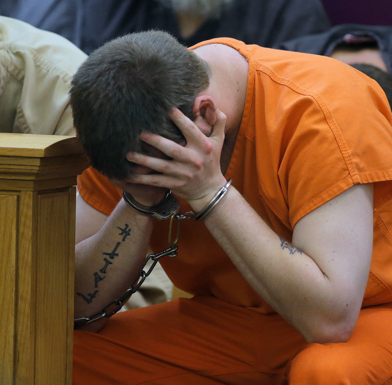Bryan Wood of Lewiston holds his head in his hands before being arraigned on three counts of arson Monday in Lewiston District Court.