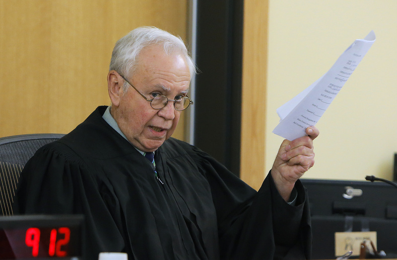 Judge John Beliveau holds a copy of an affidavit from defendant Brian Morin during Moran's arraignment Monday in Lewiston District Court on three counts of arson.