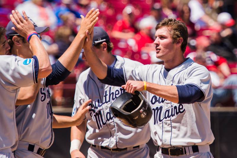 Jake Glauser is welcomed to the dugout after scoring the go-ahead run in the top of the 10th inning during University of Southern Maine's first-round game in the Division III Baseball Championship in Appleton, Wis., on Friday.