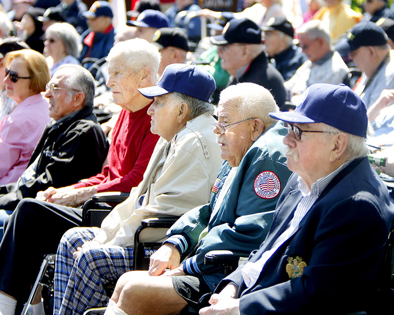 Maine Veterans' Home residents, many in wheelchairs, watch the Scarborough Memorial Day ceremony Monday morning.