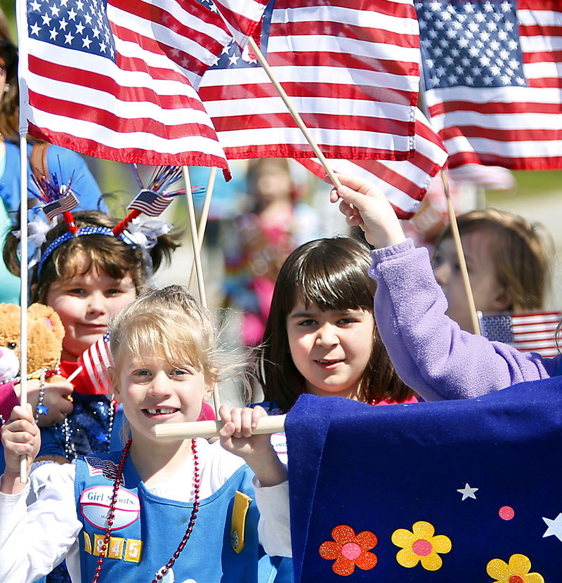 Members of Girl Scout Troop 1845 wave their American flags as they walk in the Scarborough Memorial Day parade and ceremony Monday morning.