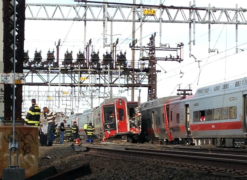 Emergency workers arrive at the scene of a train collision Friday in Fairfield, Conn. The railroad said a train derailed and was hit by the second train.