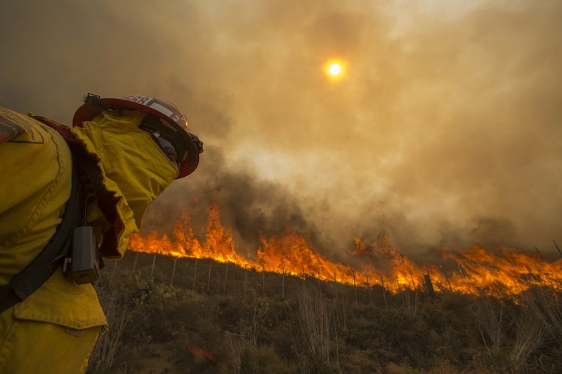 A firefighter keeps watch as the wildfire burns along a hillside in Point Mugu, Calif. Friday, May 3, 2013. Firefighters got a break as gusty winds turned into breezes, but temperatures remained high and humidity levels are expected to soar as cool air moved in from the ocean and the Santa Ana winds retreated. (AP Photo/Ringo H.W. Chiu)