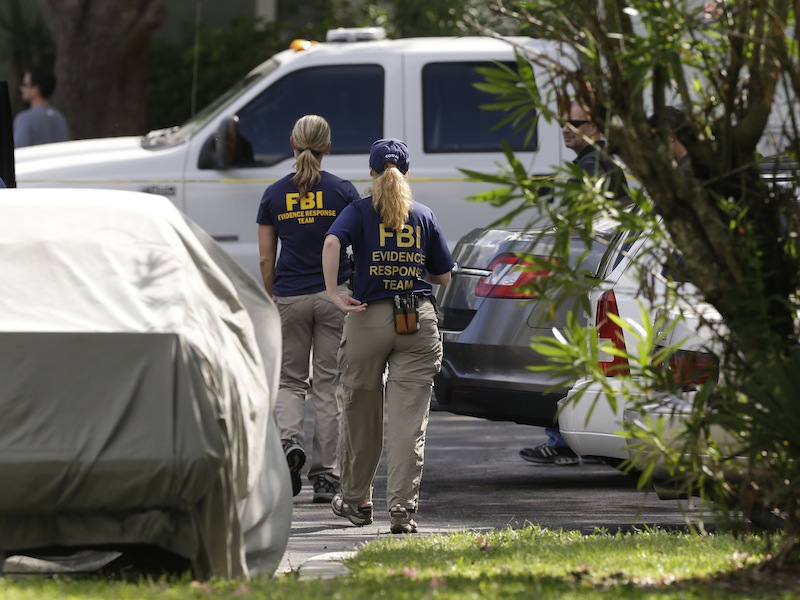FBI investigators walk near the crime scene of an apartment where a man was shot by an FBI agent, Wednesday, May 22, 2013, in Orlando, Fla. The man who was shot and killed by the agent early this morning was friends with the Boston bombings suspects, according to a friend of the victim. (AP Photo/John Raoux)