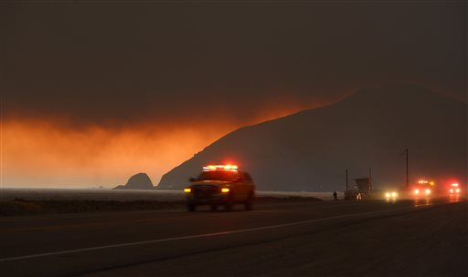 Fire department personnel drive along Pacific Coast Highway near Point Mugu as a thick layer of smoke sits overhead during a wildfire that burned several thousand acres on Thursday in Ventura County, Calif.