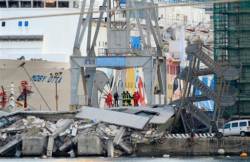 Rescue personnel stand on rubble next to a tilted staircase, part of a control tower that collapsed after a cargo ship slammed into it Tuesday night in the port of Genoa, northern Italy.