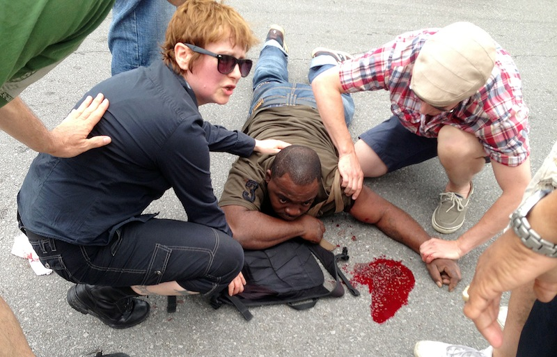 Bystanders comfort a shooting victim while awaiting EMS at the intersection of Frenchmen and N. Villere Streets after authorities say gunfire injured at least a dozen people, including a child, at a Mother's Day second-line parade in New Orleans on Sunday, May 12, 2013. No deaths were reported. (AP Photo/The Times-Picayune, Lauren McGaughy)
