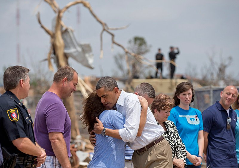 President Barack Obama embraces a school official as he views the devastation of the Plaza Towers Elementary School, Sunday, May 26, 2013, in Moore, Okla., caused by tornado and severe weather last week.