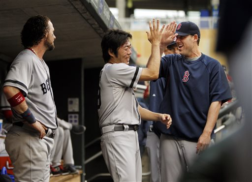Boston Red Sox relief pitcher Koji Uehara, center, is congratulated by starting pitcher John Lackey, right, as catcher Jarrod Saltalamacchia, left, looks on Sunday in Minneapolis.