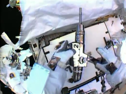 In this image made from video provided by NASA, astronaut Christopher Cassidy, foreground, holds a power wrench as he stows away a suspect coolant pump on the International Space Station on Saturday. Thomas Marshburn is at left. The two astronauts made the spacewalk to replace the pump after flakes of frozen ammonia coolant were spotted outside the station on Thursday.