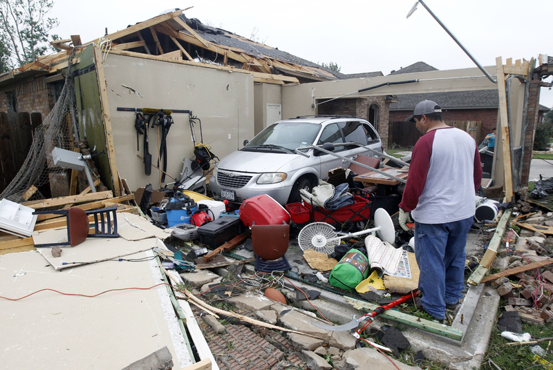 Pete Alaniz looks for items to salvage Thursday after a tornado hit his home in Cleburne, Texas. His family of four and three dogs hid in a closet while the tornado destroyed his home. A rash of tornadoes slammed into several small communities in North Texas overnight, leaving at least six people dead, dozens more injured and hundreds homeless.