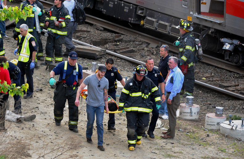 Injured passengers are transported from the scene where two Metro North commuter trains collided on Friday near Fairfield, Conn.