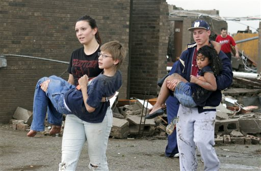 Teachers carry children away from Briarwood Elementary school after a tornado destroyed the school in south Oklahoma City, Okla, Monday, May 20, 2013.