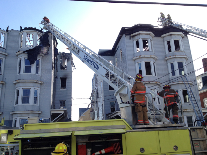 Firefighters work at the Bartlett Street apartment buildings that burned Monday morning.
