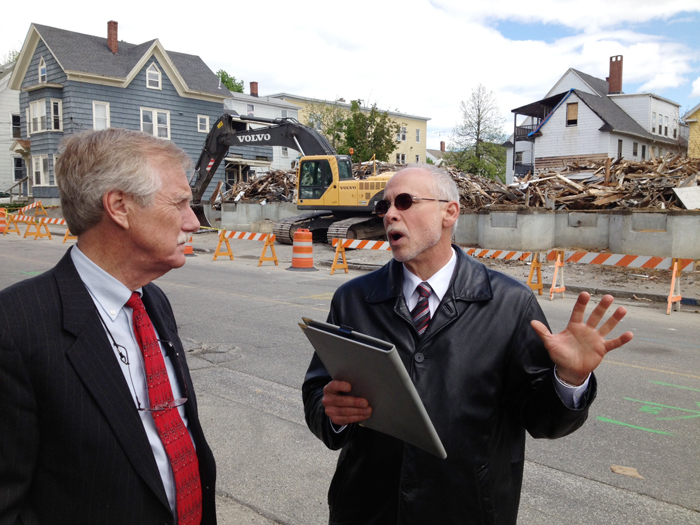 U.S. Sen. Angus King speaks with Assistant City Administrator Phil Nadeau in Lewiston as demolition work takes place on a building at 114-118 Bartlett St., which burned on May 6.