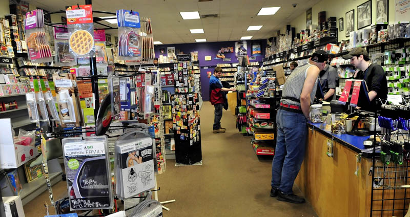 Bull Moose Music store head clerk Aaron Beckim, right, waits on customer Arthur Ellis at the store in the Elm Plaza in Waterville. The business is expanding into the adjacent former Mr. Paperback location.