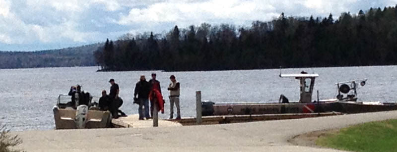 Maine Warden Service divers search Rangeley Lake on Thursday for three snowmobilers missing since winter.