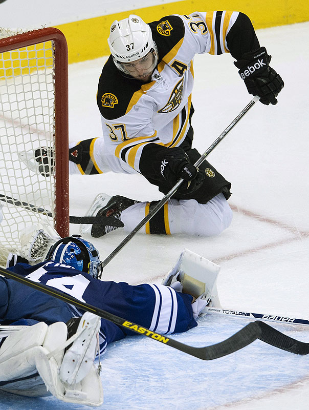 Toronto goaltender James Reimer frustrates a scoring bid by Boston forward Patrice Bergeron during second-period action of Sunday's game. Canada;Canadian;sports;play;ice hockey;game;action;competitive;c