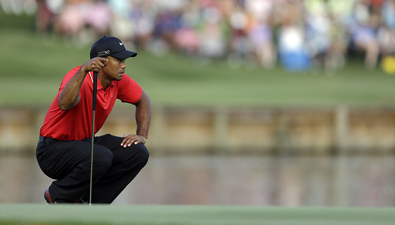 Tiger Woods looks at his putt on the 17th green during the final round of The Players Championship at TPC Sawgrass in Ponte Vedra Beach, Fla. He made par while his longtime rival Sergio Garcia hit two balls into the water before the green to fall out of contention.