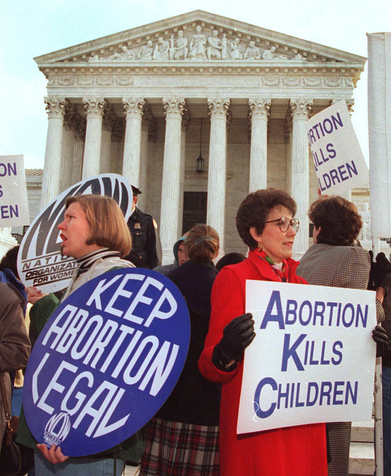 "A supporter of abortion rights and an opponent of abortion demonstrate outside the U.S. Supreme Court in 2005. The split among Americans over whether abortion should be legal ""obscures the common ground that many or most can agree on: Abortion should be rare,"" a reader says."