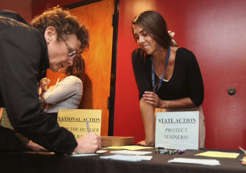Karen Wentworth, of South Portland, joined by Abby Farnham of the Preble Street Hunger Initiative, signs a card calling for action on dealing with hunger before showing of the film