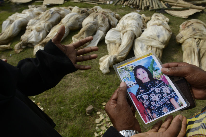 A woman shows a picture of her sister in hopes of finding her body among unclaimed remains in preparation for a mass burial on Wednesday in Dhaka, Bangladesh.