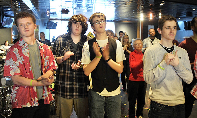 Members of the band Rupture the Fish listen to the announcements of the winners. At left is Scott Ralston, who won