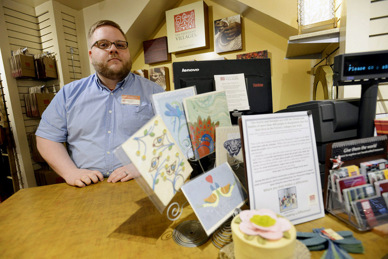 Kevin Hudson, store manager at Ten Thousand Villages on Exchange Street in Portland, sits near merchandise on display from Bangladesh along with a sign stating their support for family and friends of the victims of the factory collapse. Photographed on Thursday, May 2, 2013. The store is encouraging Fair Trade Retail and offering their support to Bangladesh in light of the recent factory collapse.