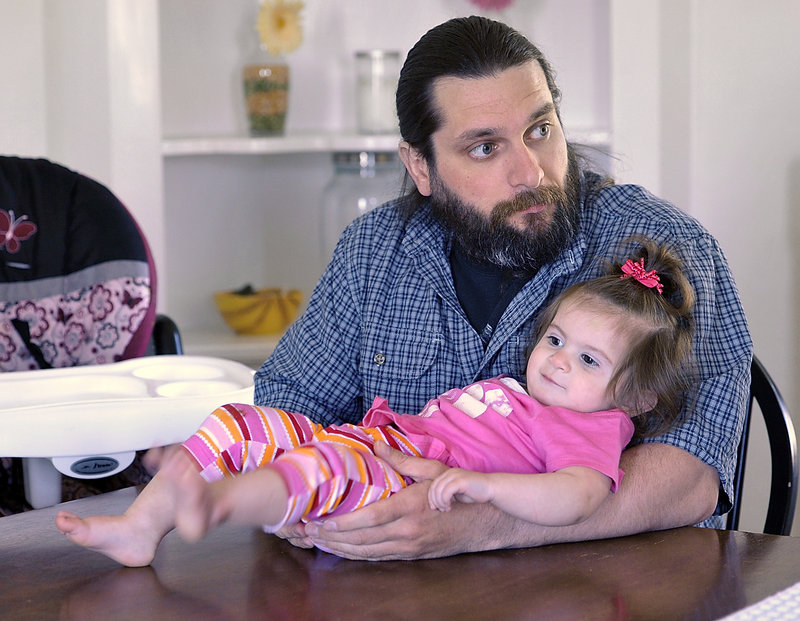 Donald Evans holds 14-month-old Willow as he listens to his wife talk about the 2011 plane crash in Alaska. Rosemarie Evans was two months pregnant at the time.