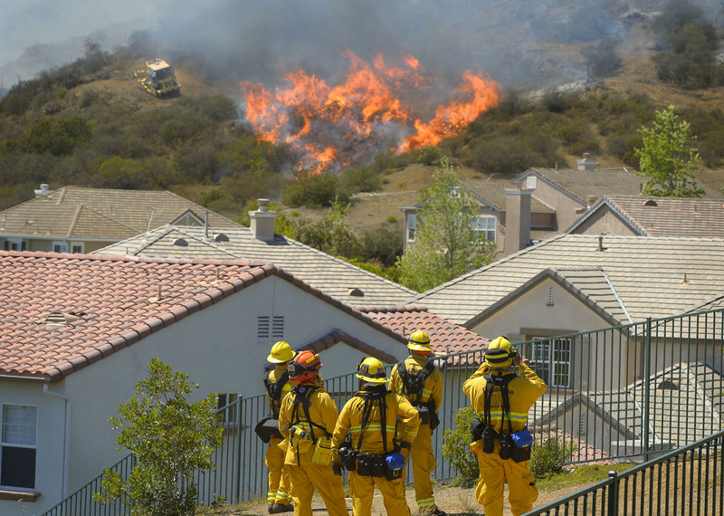 Firefighters from Glendale and Pasadena, Calif., stand watch as bulldozers clear a firebreak near a wildfire burning along a hillside near homes in Thousand Oaks, Calif., on Thursday.