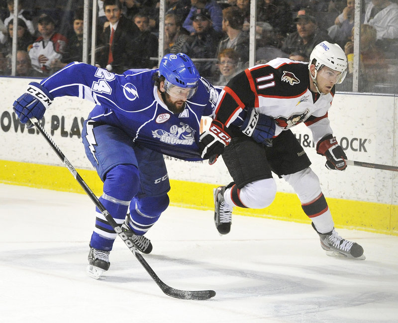 Chris Brown of the Portland Pirates, right, grabs a chunk of sweater of Jean-Philippe Cote of the Syracuse Crunch while chasing the puck in the corner Thursday night.