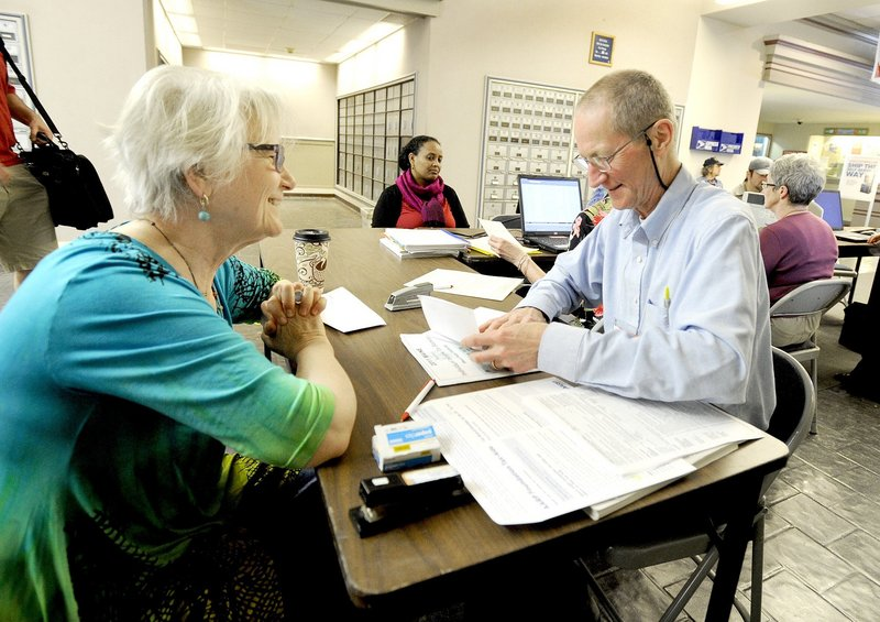 R.J. Harper, right, an IRS-certified volunteer tax preparer, helps last-minute filer Ana Dana at Portland's Forest Avenue post office on April 17, 2012. A proposal to reform Maine's tax system is a long shot, given its timing, but it demands serious consideration from legislators and Gov. LePage.