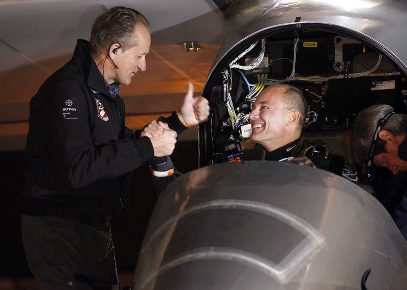 Andre Borschberg, left, and Bertrand Piccard shake hands before the Solar Impulse plane takes off on a multi-city trip across the United States.