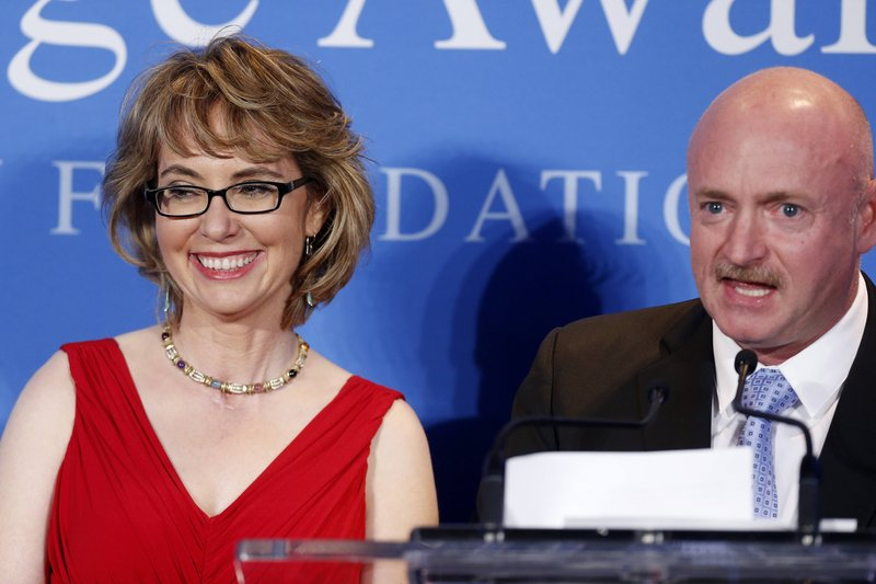 Mark Kelly speaks beside his wife, former Arizona U.S. Rep. Gabrielle Giffords, after Giffords received the John F. Kennedy Profile in Courage Award at the JFK Library in Boston on Sunday.