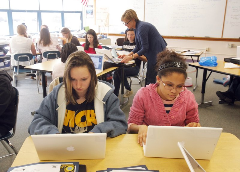 Students Jessy Brewer, left, and Kiara Neal work on their laptops at King Middle School in Portland in 2012. Apple's exclusive contract to provide laptops to Maine middle school students is coming to an end. Readers are skeptical about the move to HP and Windows 8.