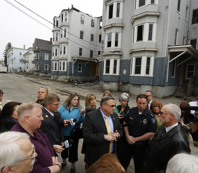 """Gov. Paul LePage talks to the media Tuesday while meeting with Lewiston officials in front of two buildings that burned Monday on Bartlett Street. Asked if he was happy to be back in his hometown, where he was homeless as a youth for two years, he said, """"It brings back a lot of bad memories."""""""