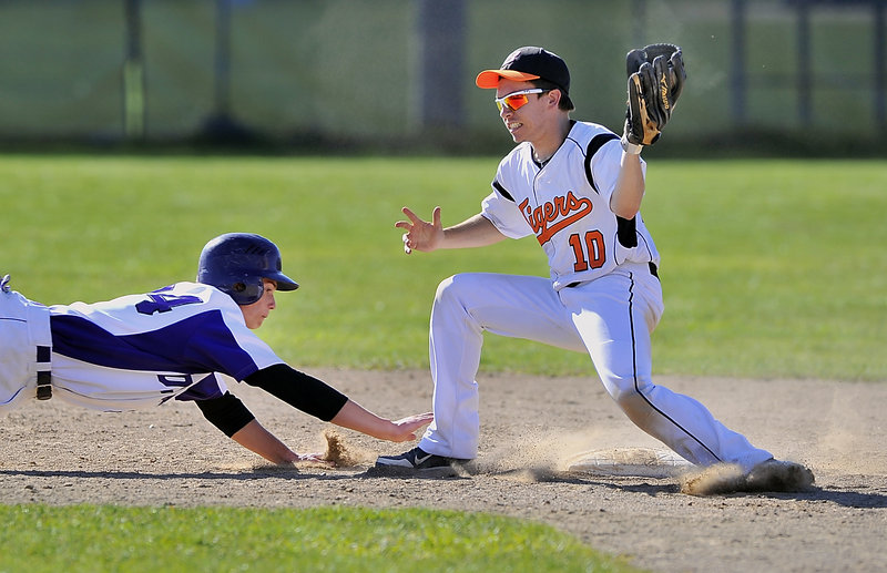 Will Barlock of Deering dives for the safety of the second-base bag Tuesday as Corey Collard of Biddeford takes the throw from the catcher during their SMAA game. Biddeford scored in the bottom of the seventh inning for a 5-4 victory.